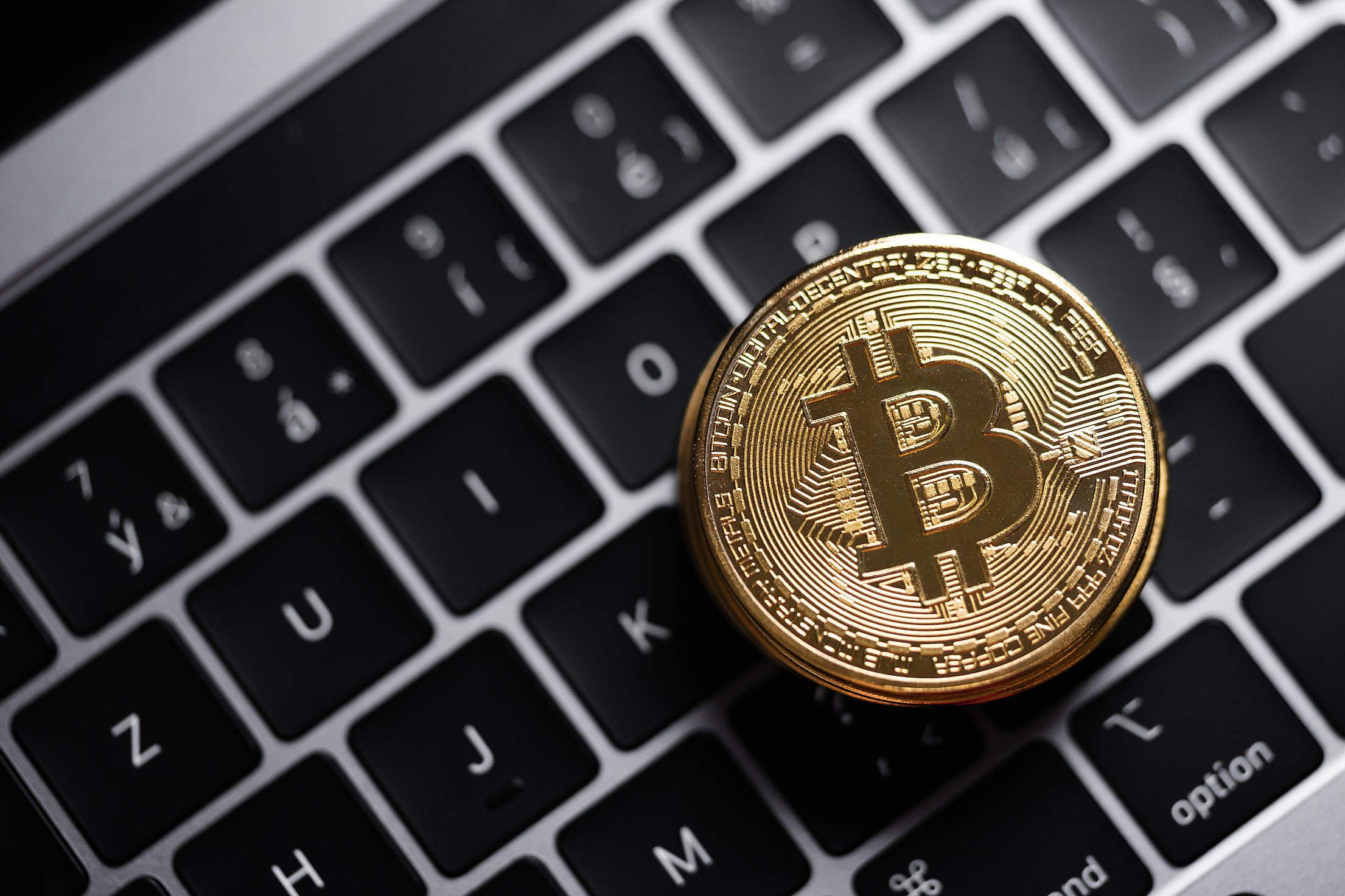 Golden Bitcoin on a MacBook Keyboard Free Stock Photo