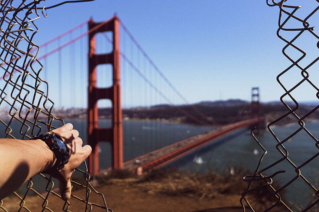 Download Golden Gate Bridge Through a Hole in a Fence FREE Stock Photo
