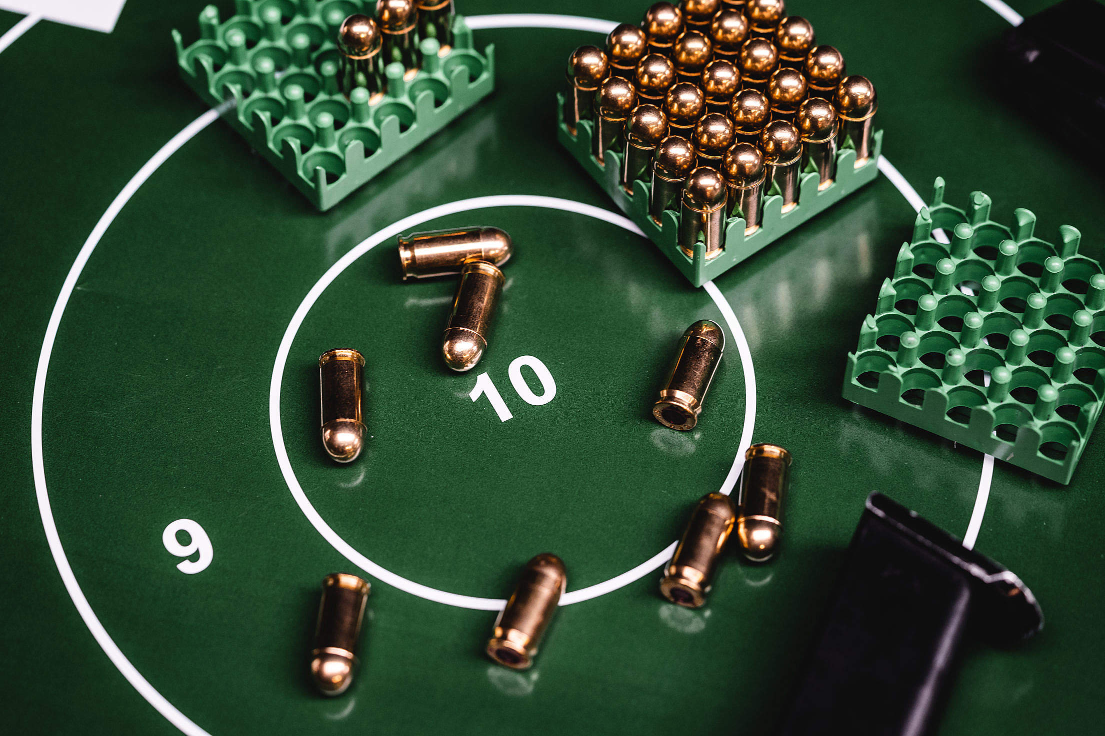 Green Shooting Target with a Lot of 9mm Ammunition Free Stock Photo