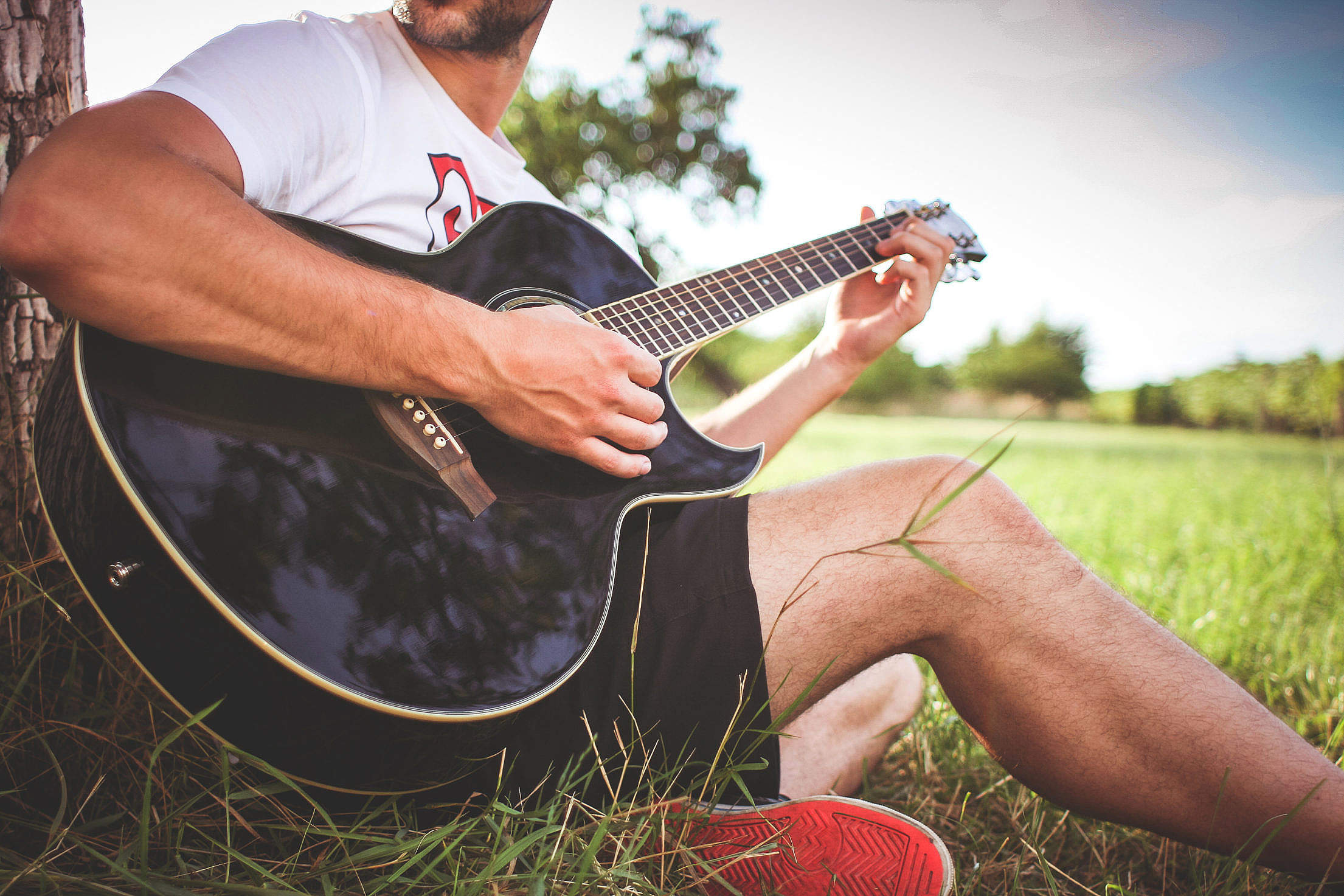 Guy Playing Acoustic Guitar in Nature Free Stock Photo