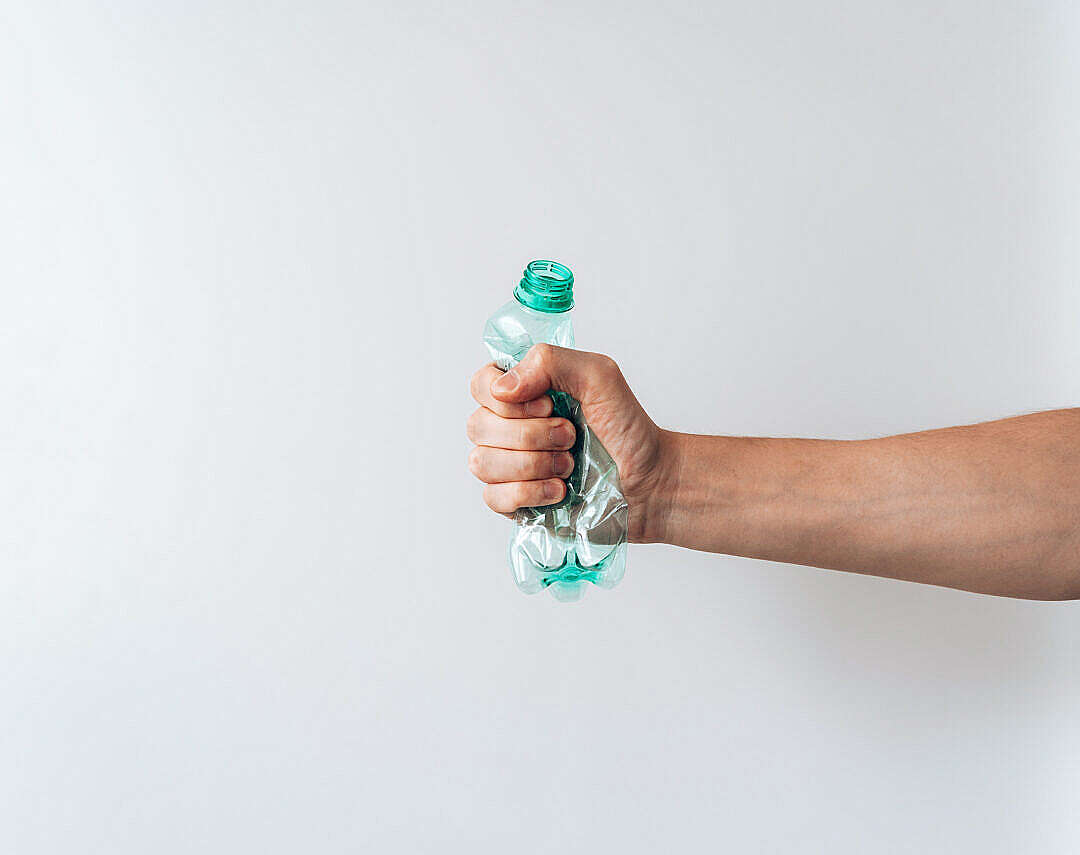 Download Hand Holding a Crumpled Plastic Bottle FREE Stock Photo