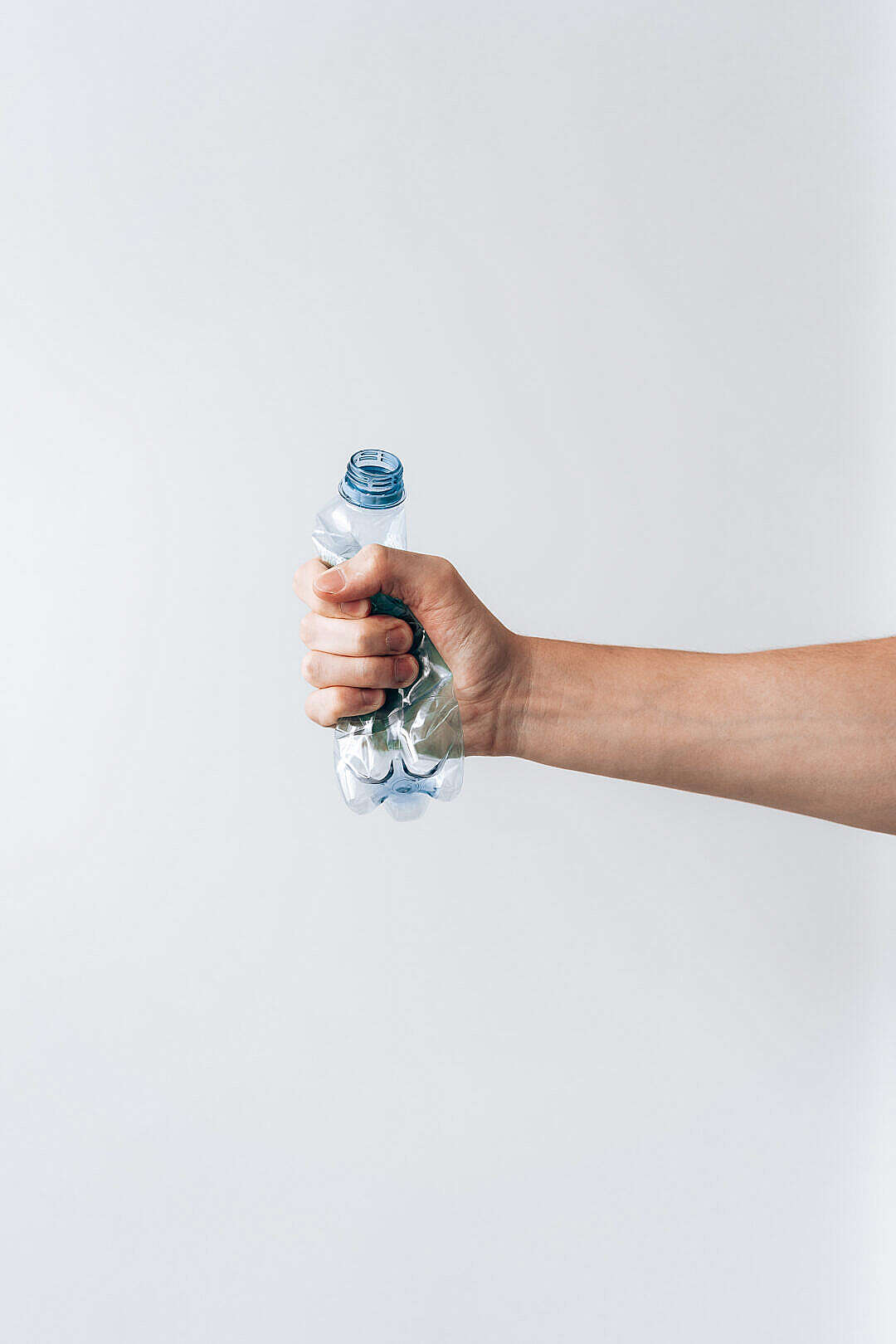 Download Hand Squeezing Empty Plastic Water Bottle FREE Stock Photo