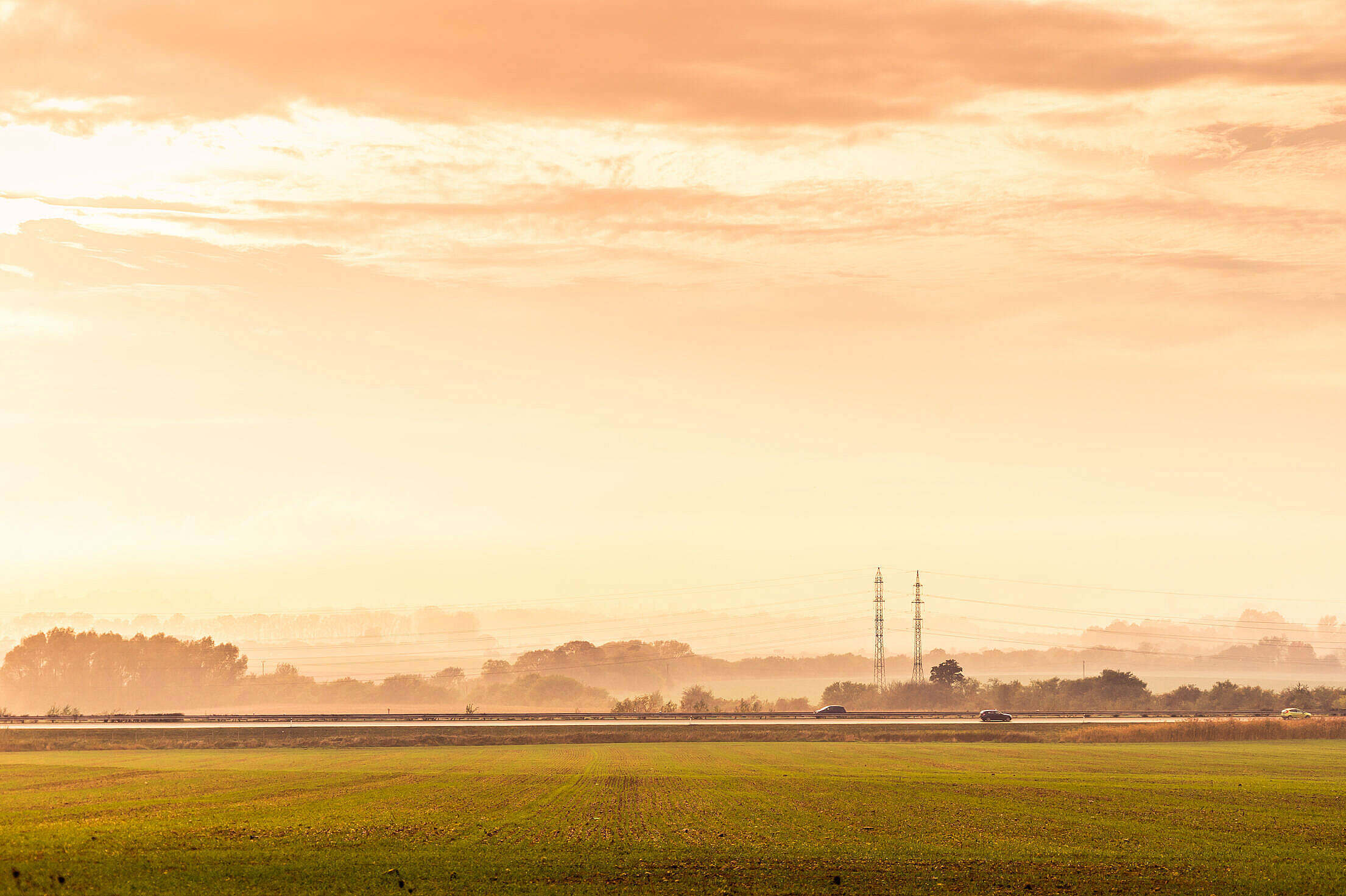 Highway Road with Cars and Electricity Pylons Foggy Golden Hour Free Stock Photo