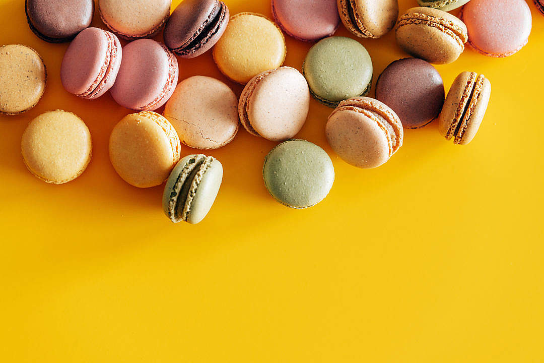 Download Homemade Colorful Macarons on Yellow Background FREE Stock Photo