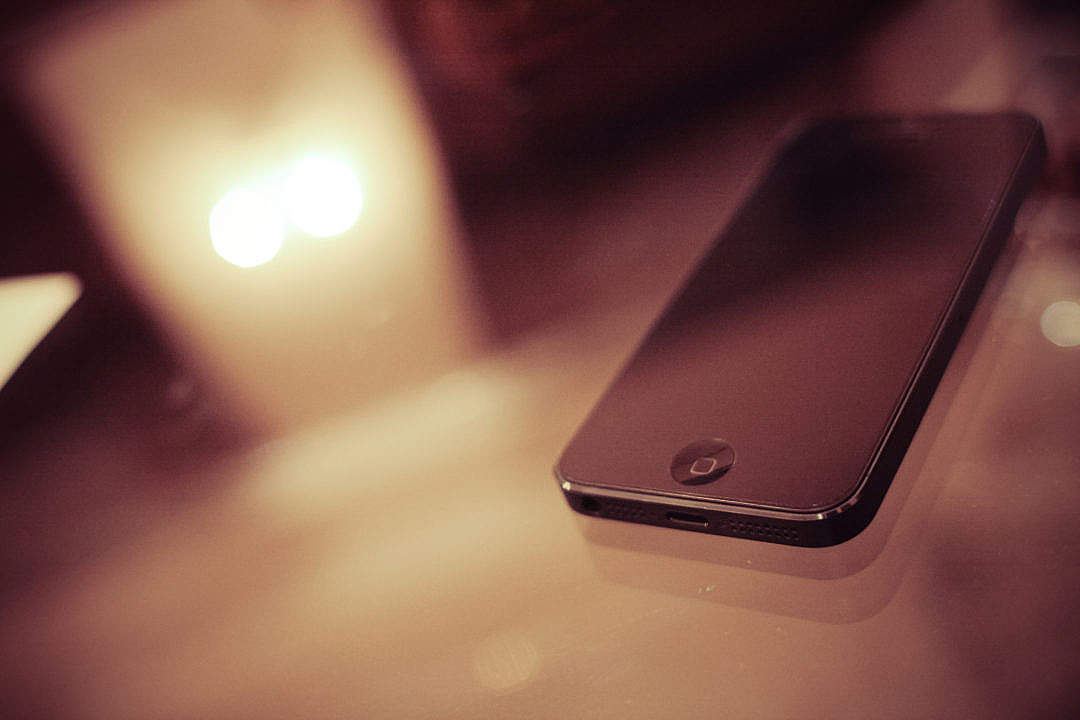 Download iPhone 5 on a Glass Table FREE Stock Photo