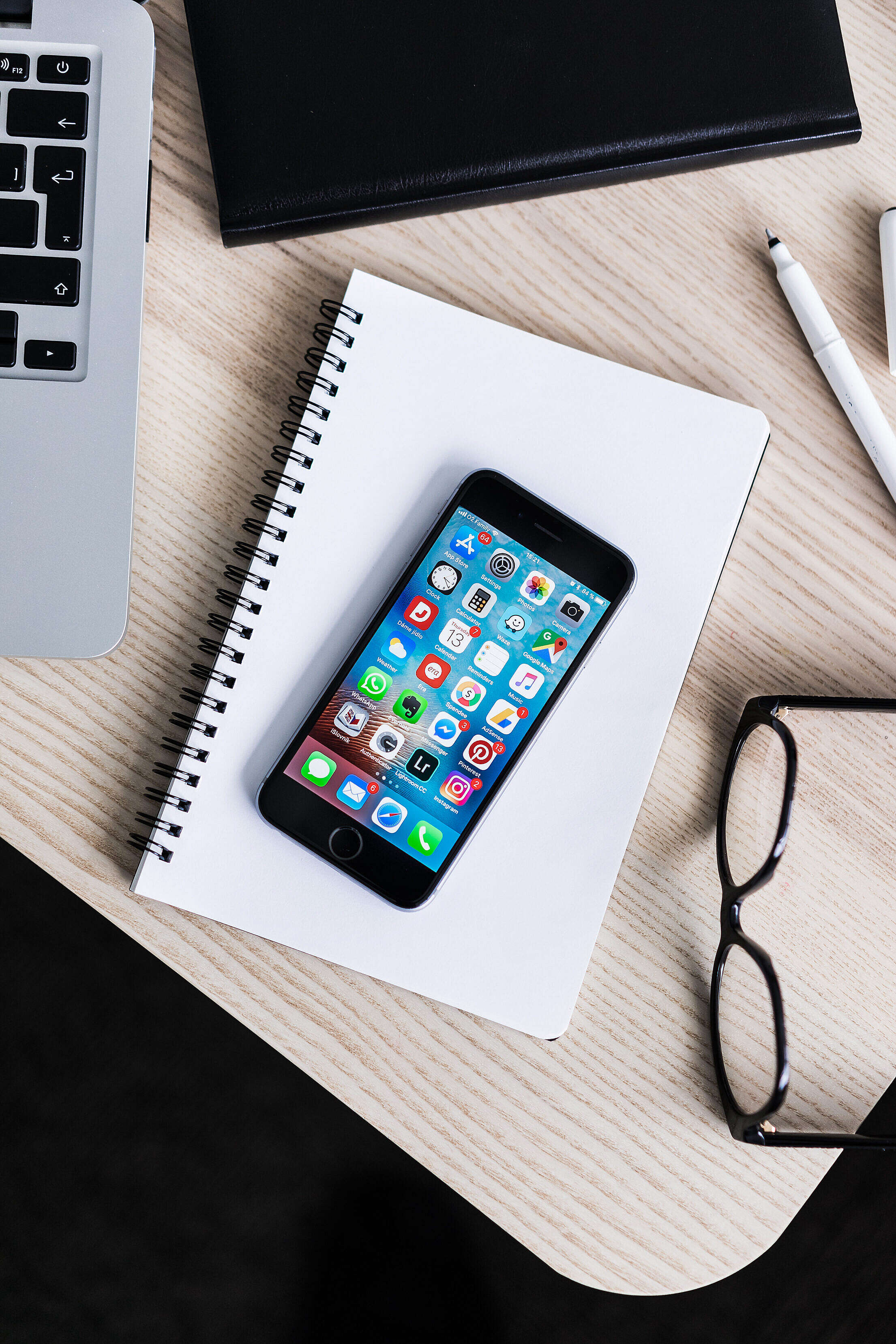 iPhone Lying on Notebook and Wooden Desk Mockup Free Stock Photo