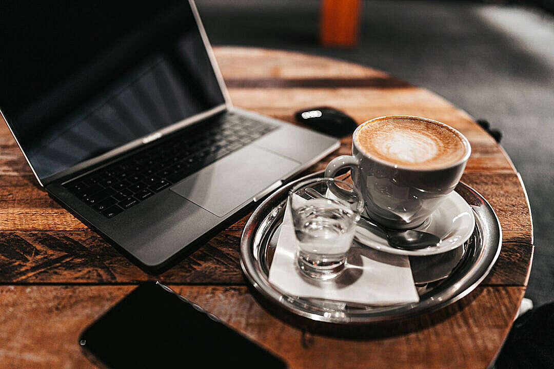 Download Laptop and Cappuccino on a Wooden Table FREE Stock Photo
