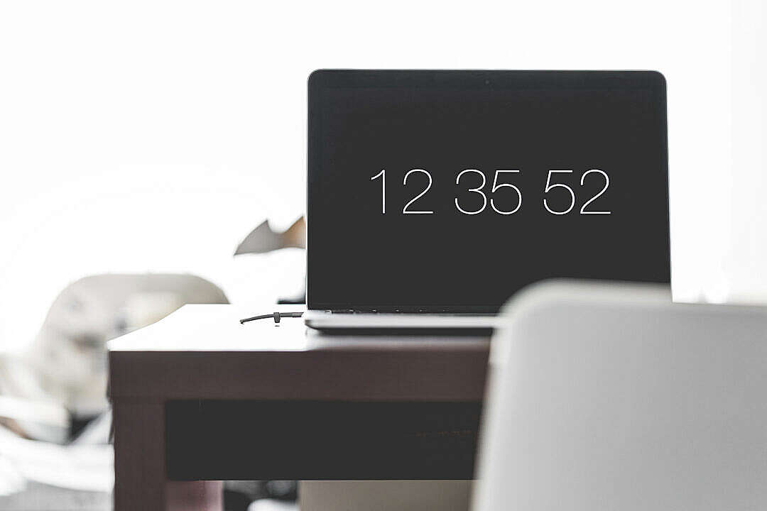 Download Laptop with Time Screen Saver on Office Desk FREE Stock Photo