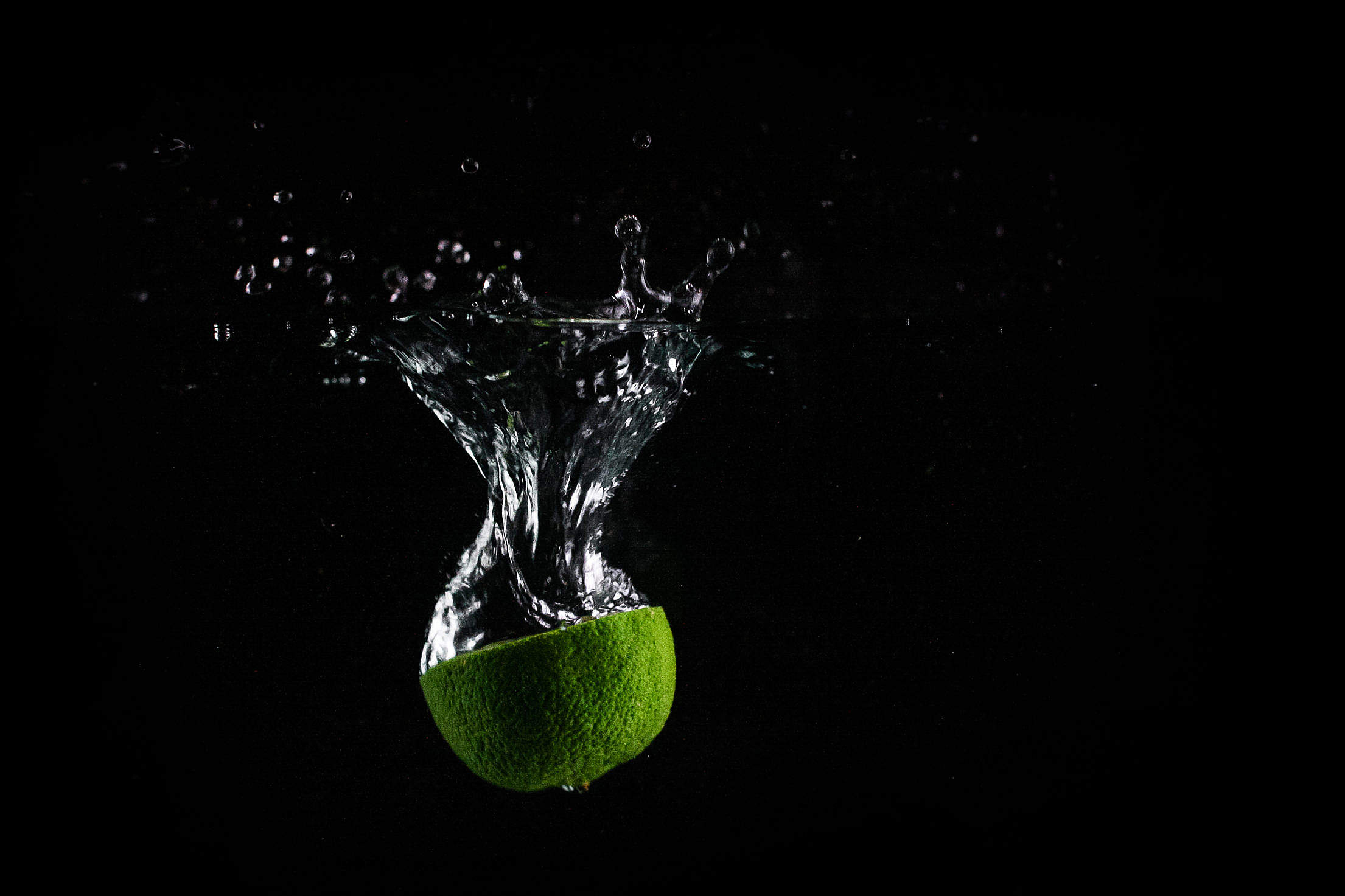 Lime In Water with Black Background Free Stock Photo