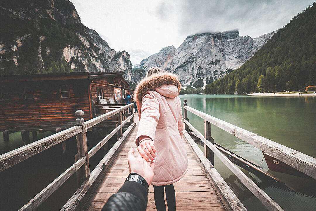 Download Lovely Couple in Follow Me To Pose on Braies Lake Pier, Italy FREE Stock Photo
