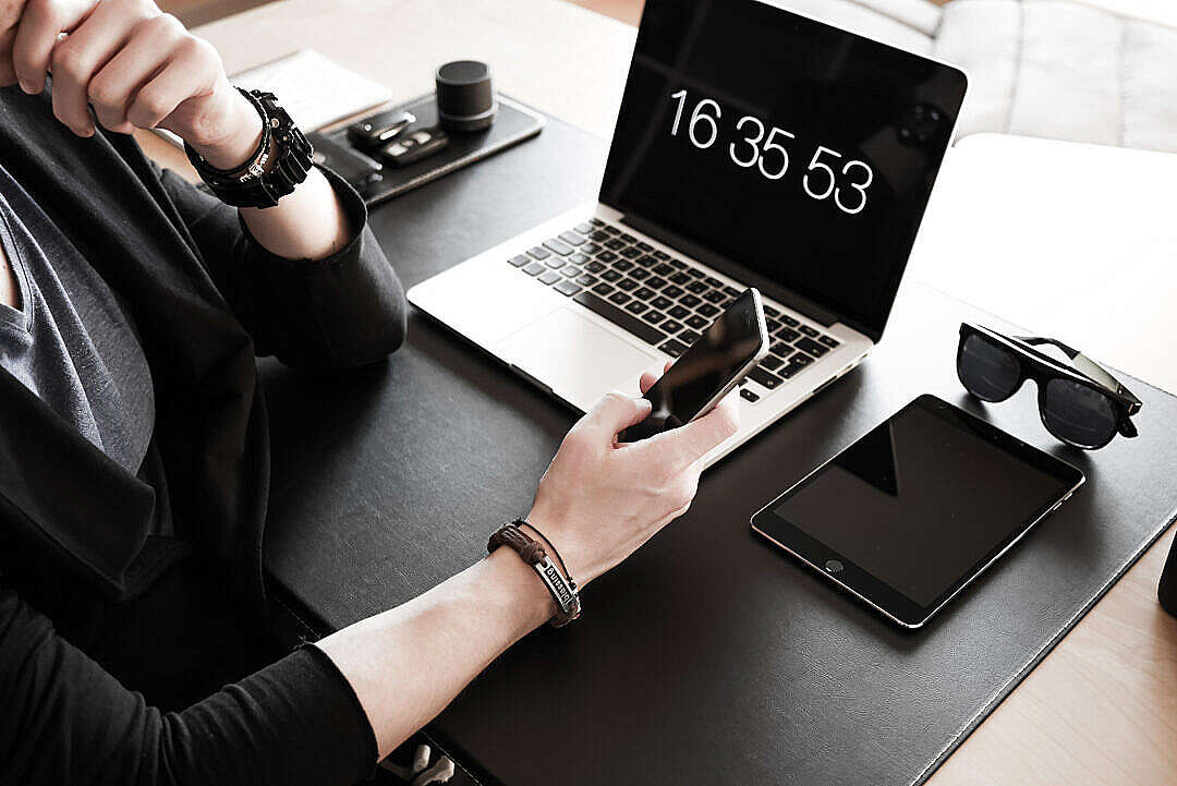 Download Man Checking His iPhone & Working at Home Office FREE Stock Photo