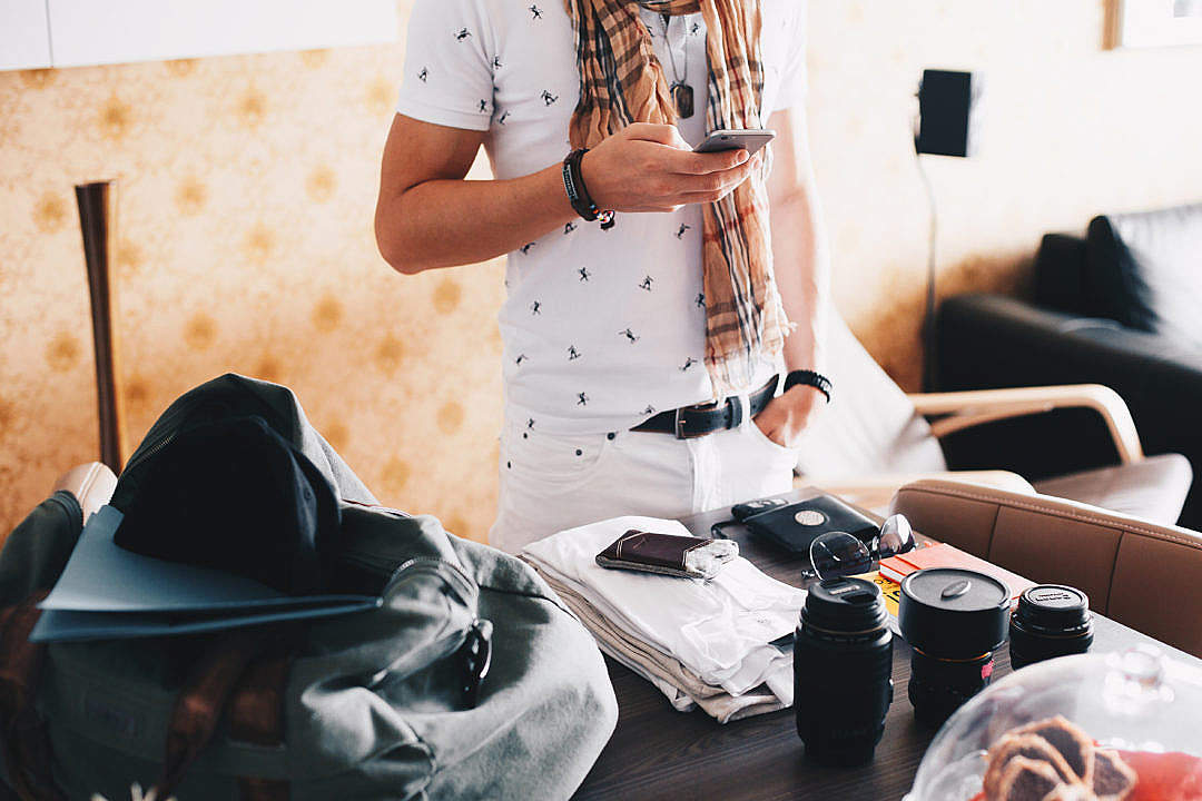 Download Man Checking His Phone while Packing for a Trip FREE Stock Photo