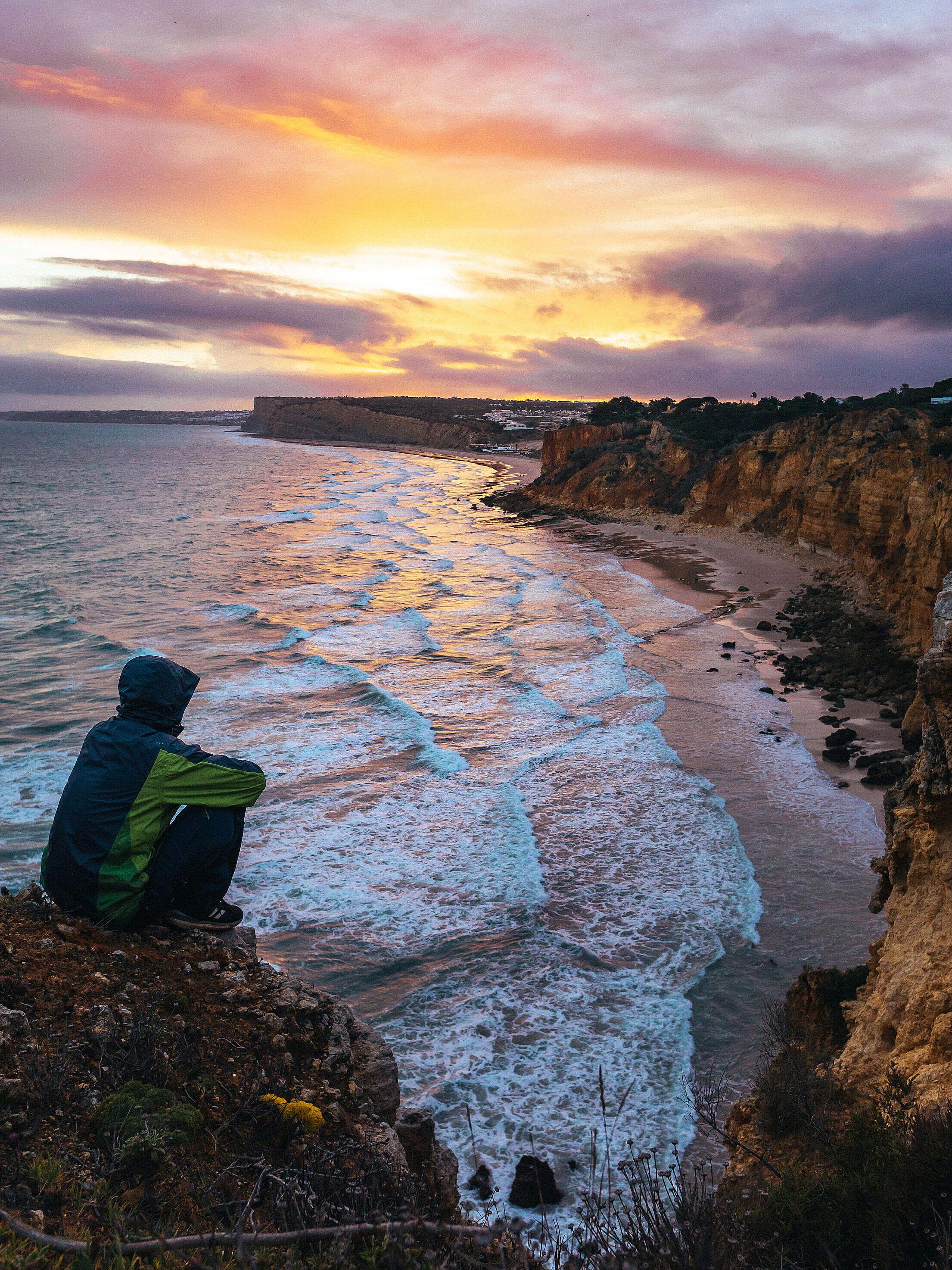 Man Enjoying Cloudy Sunset by Portugal Coastline Free Stock Photo