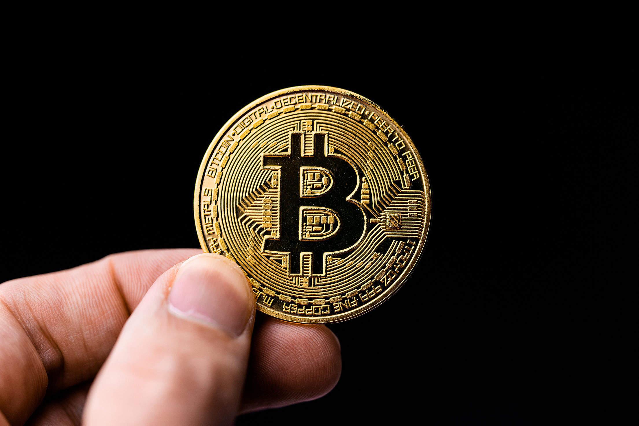 Man Holding a Bitcoin Coin Free Stock Photo
