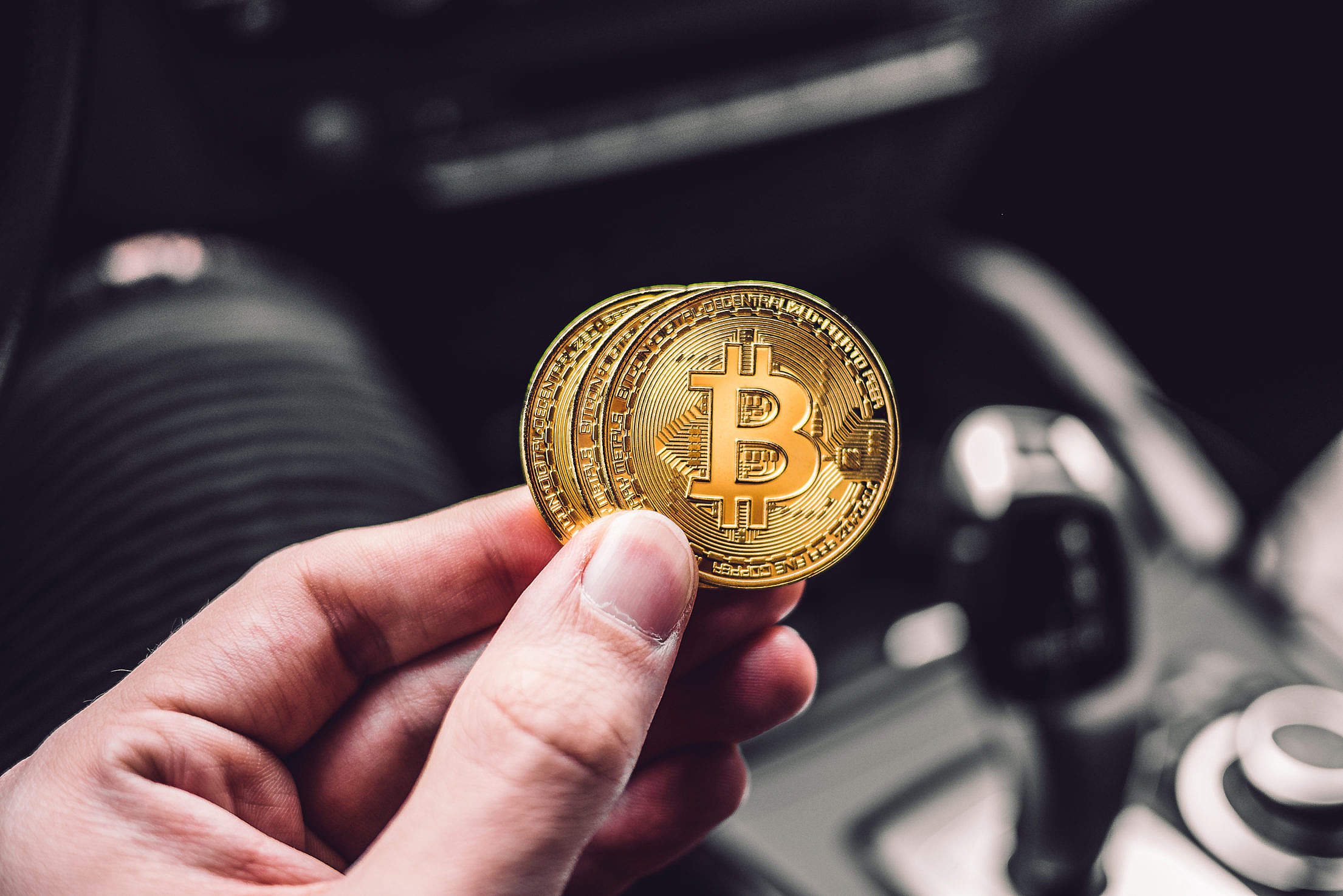 Man Holding a Bitcoin Coin in a Car Free Stock Photo