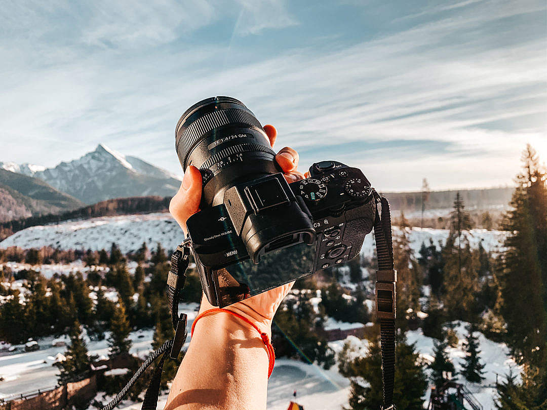 Download Man Holding a Camera in Mountains FREE Stock Photo