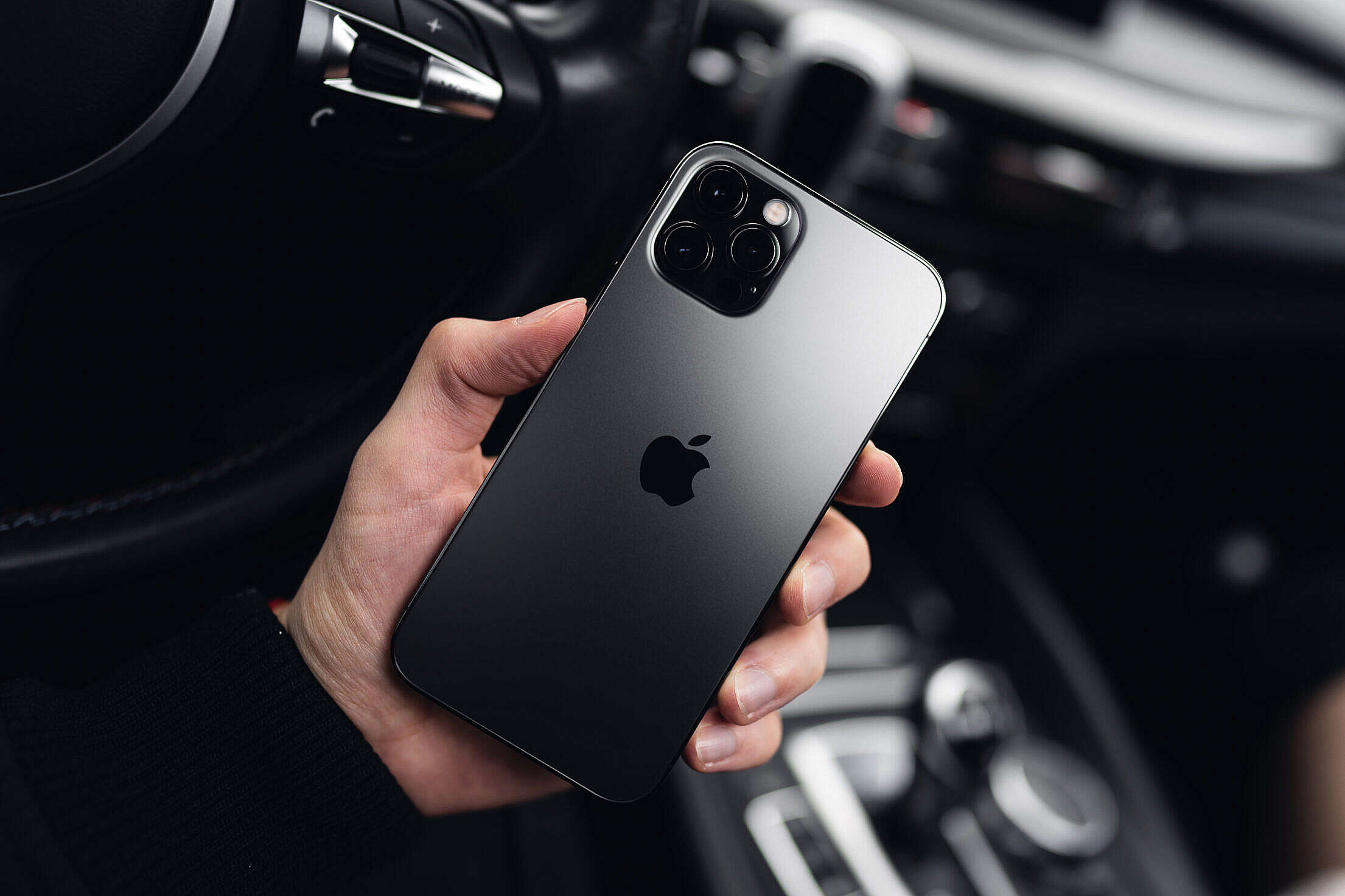 Man Holding a New iPhone 12 Pro in a Car Free Stock Photo
