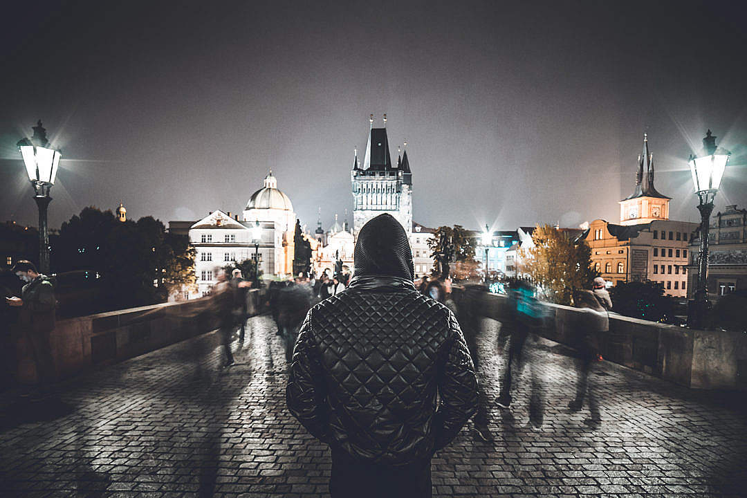 Download Man in a Hoodie Standing Still Against Crowds on Charles Bridge, Prague FREE Stock Photo