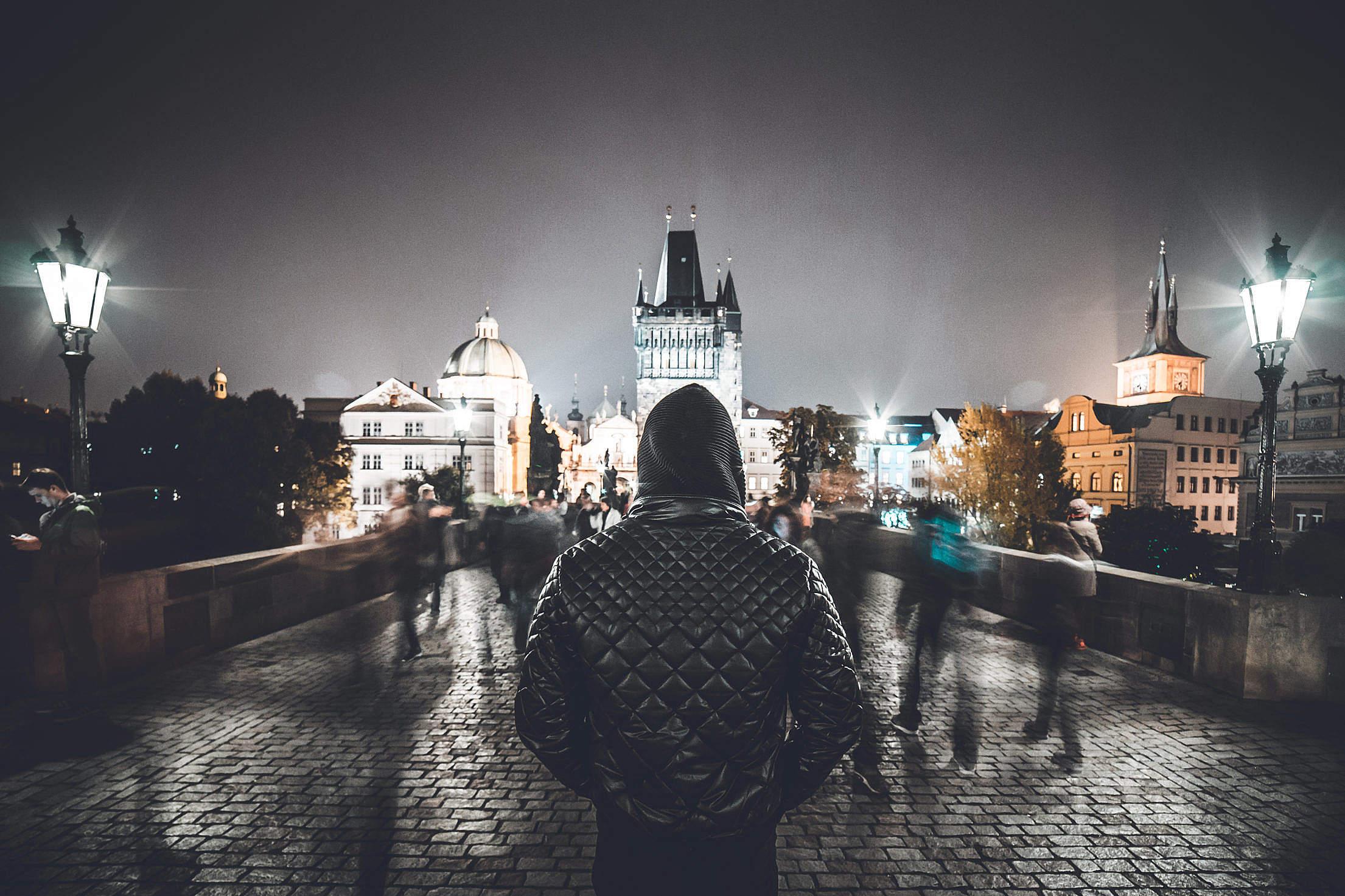 Man in a Hoodie Standing Still Against Crowds on Charles Bridge, Prague Free Stock Photo