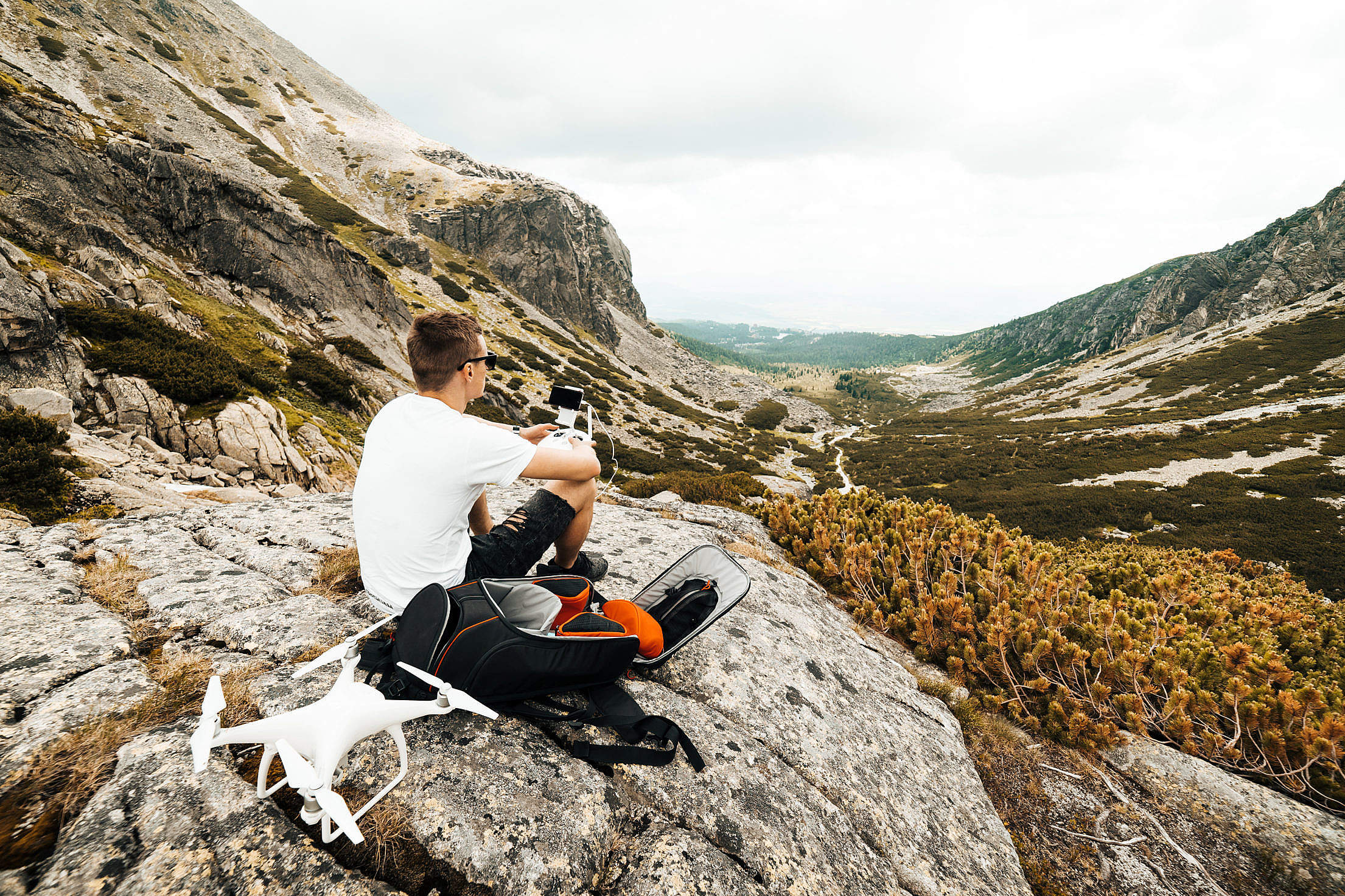 Man Setting Up a Drone for Aerial Photography in Mountains