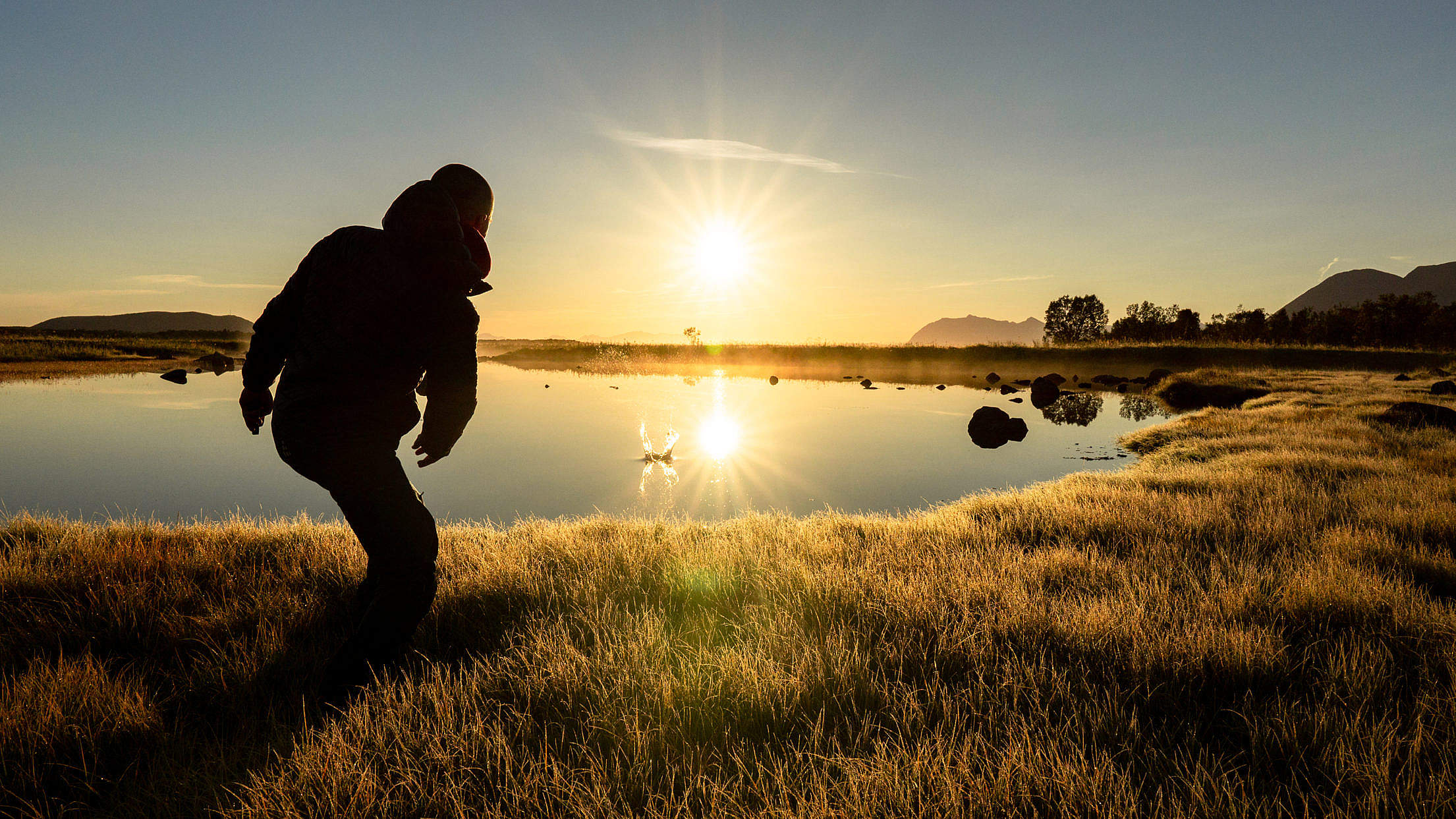 Man Throwing a Stone into a Calm Lake During Beautiful Sunrise Free Stock Photo
