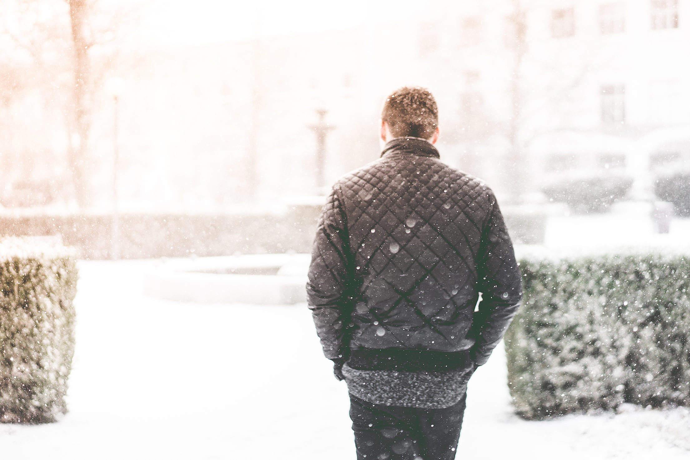 Man Walking in Snowfall Free Stock Photo