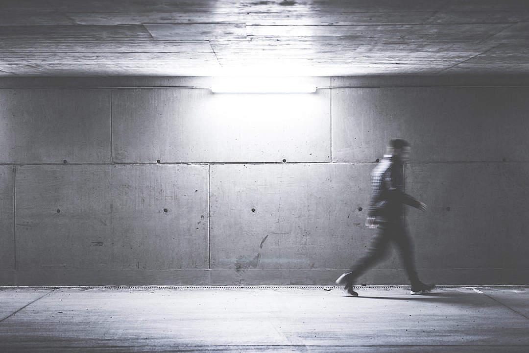 Download Man Walking Through Concrete Underpass FREE Stock Photo