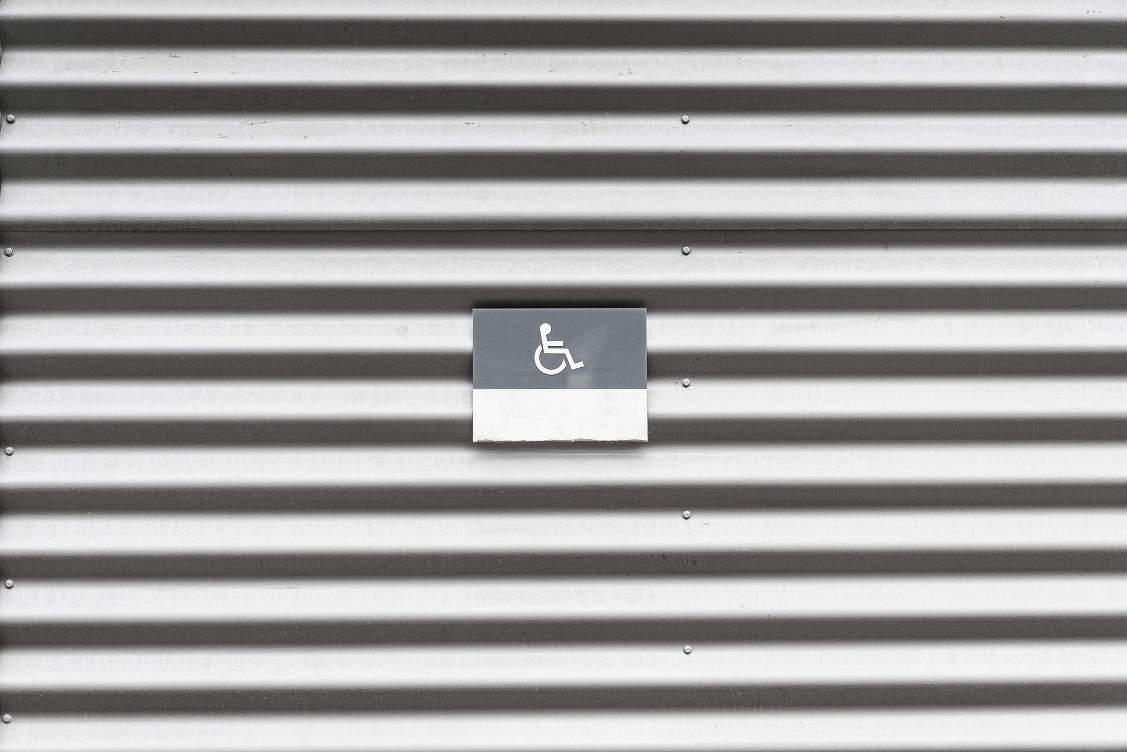 Metal Wall with Wheelchair Disabled Sign Free Stock Photo