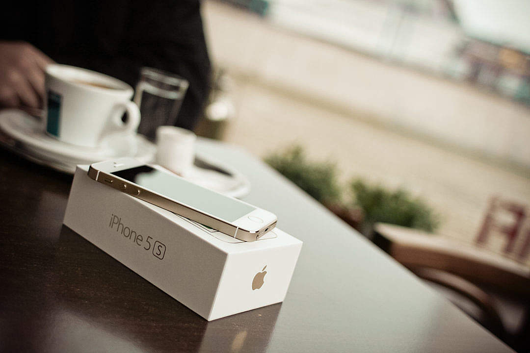 Download New iPhone 5S Gold in cafe FREE Stock Photo