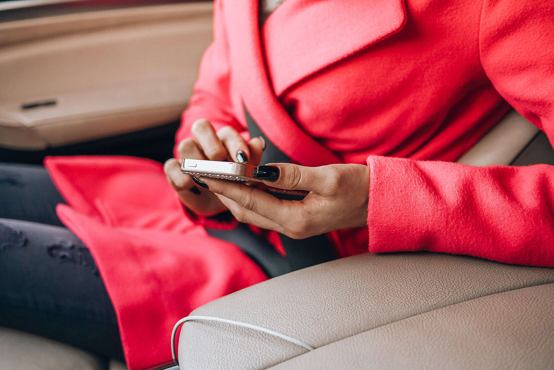Nicely Dressed Woman Using Her Phone in a Car Free Stock Photo