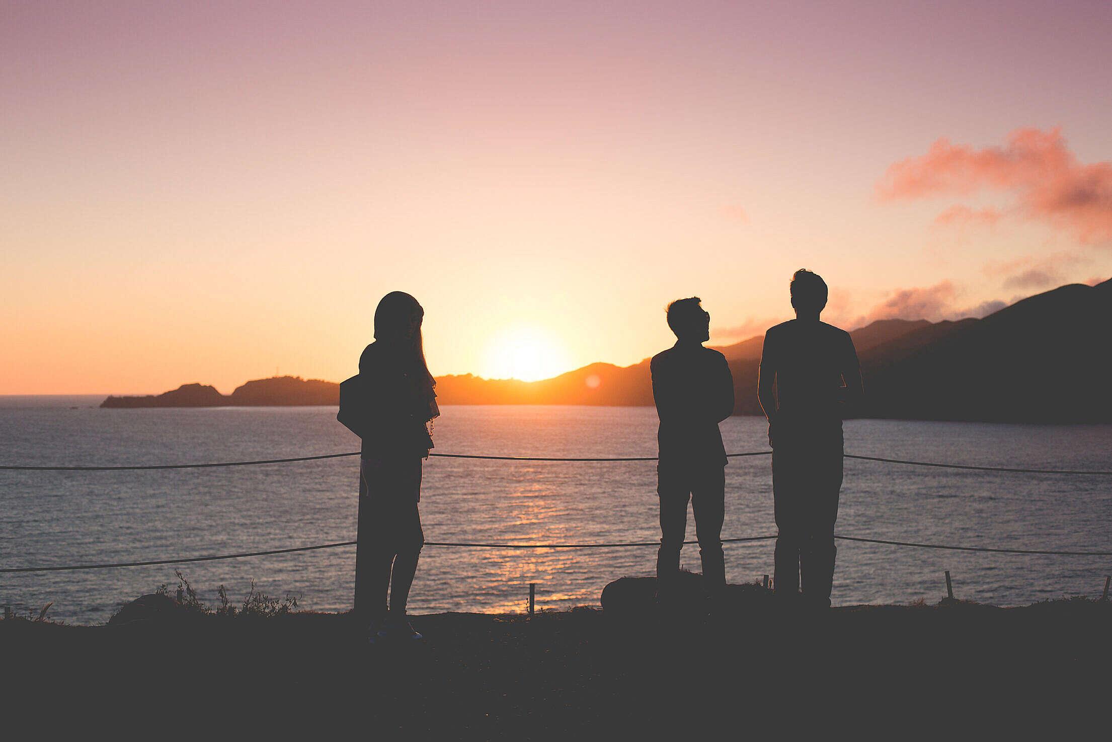 People Enjoying Sunset Over the Ocean Free Stock Photo