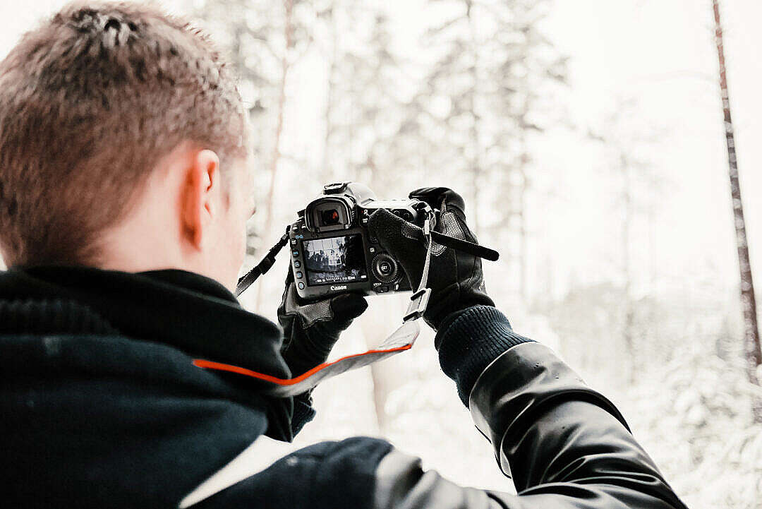 Download Photographer in Snowy Forest Taking Winter Photos FREE Stock Photo