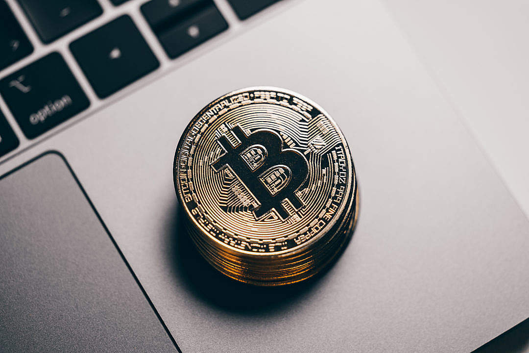 Download Pile of Bitcoins on a Laptop FREE Stock Photo