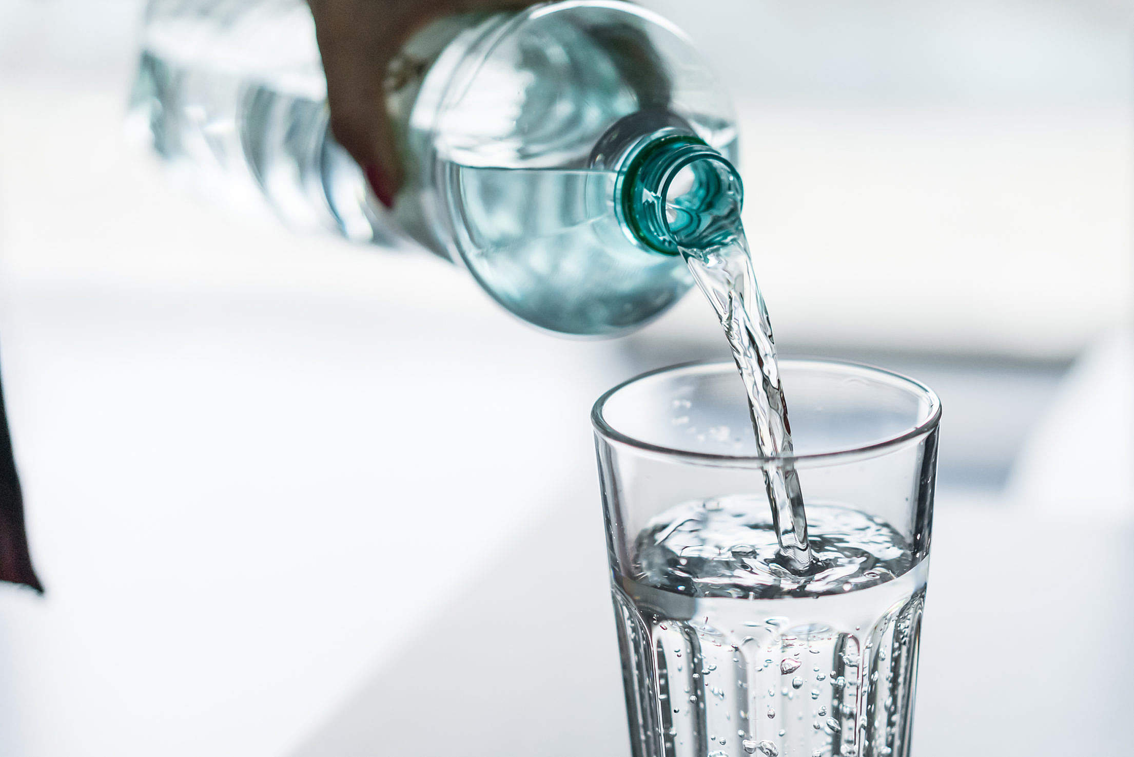 Pouring Water from PET Bottle into a Glass Free Stock Photo