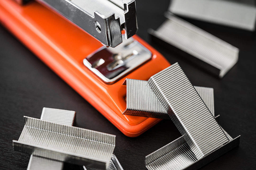 Download Red Office Stapler and Pile of Copper Office Staples FREE Stock Photo