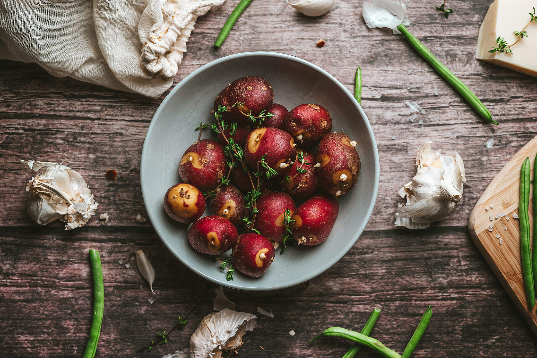 Red Potatoes with Thyme on a Rustic Table Free Stock Photo