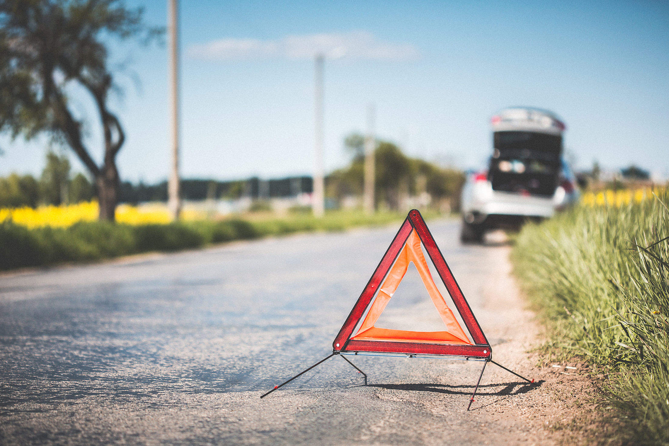 Red Warning Triangle and Broken Car on The Road Free Stock Photo