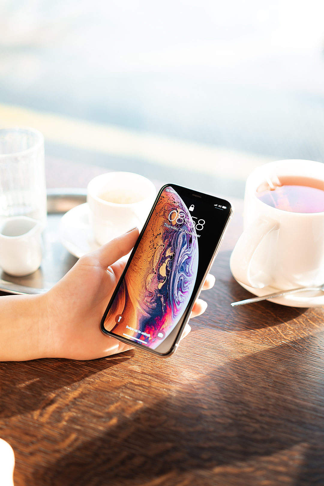 Download Showing an iPhone XS in Café FREE Stock Photo