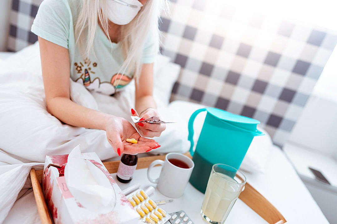 Download Sick Woman Sitting in a Bed and Taking Medications FREE Stock Photo
