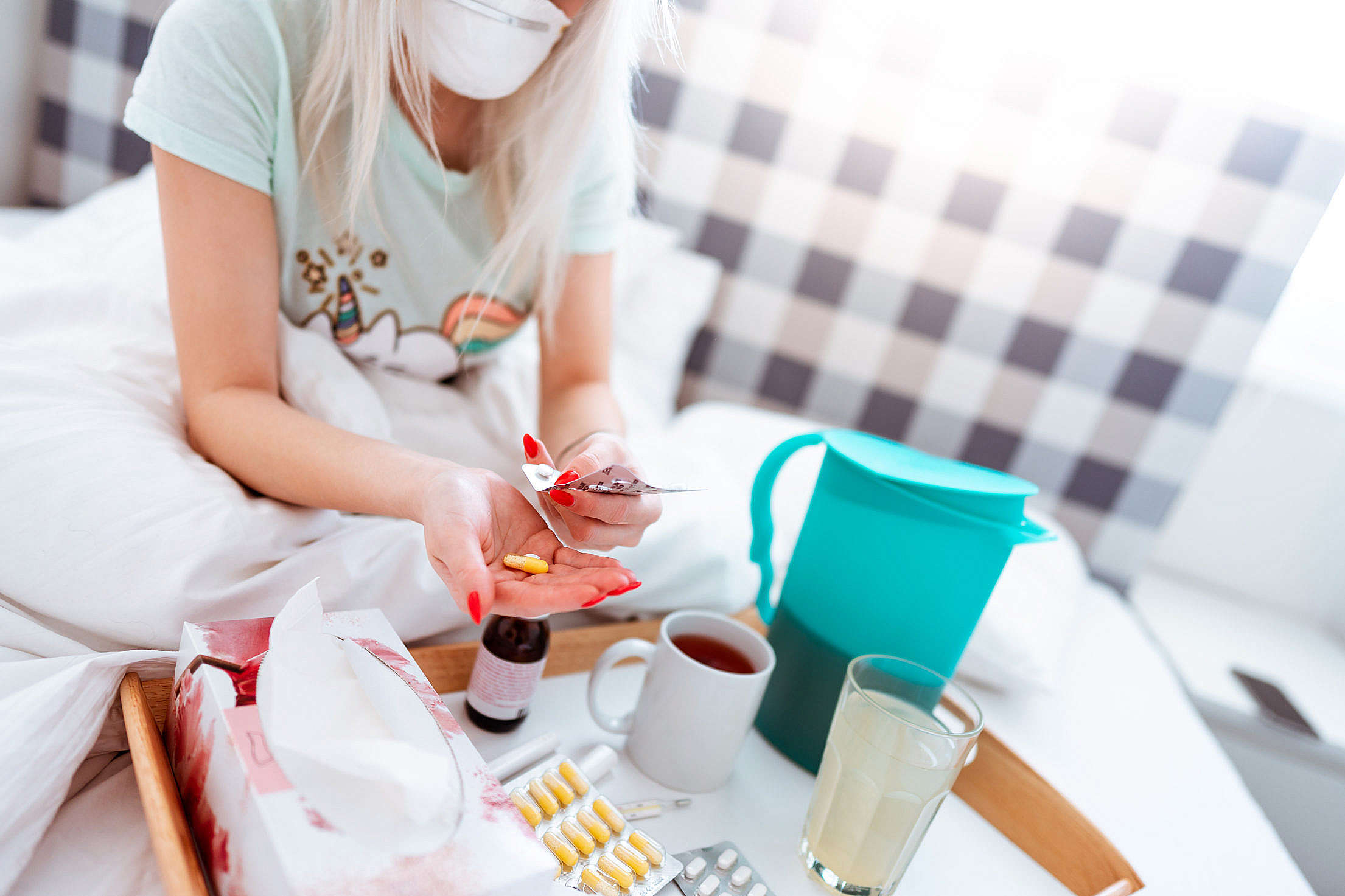 Sick Woman Sitting in a Bed and Taking Medications Free Stock Photo