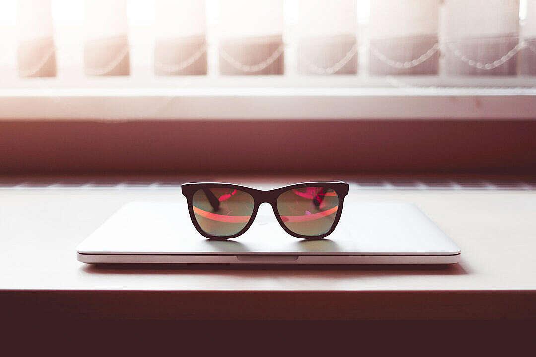 Download Sleek Sunglasses on Closed MacBook Laptop FREE Stock Photo