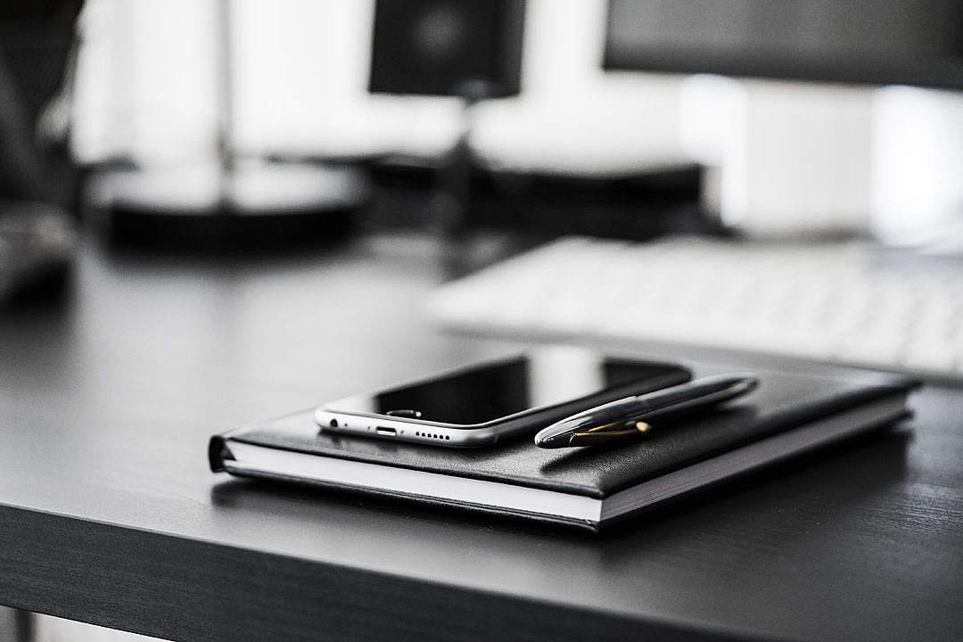 Download Smartphone, Diary and Silver Pen on Black Workspace Desk FREE Stock Photo