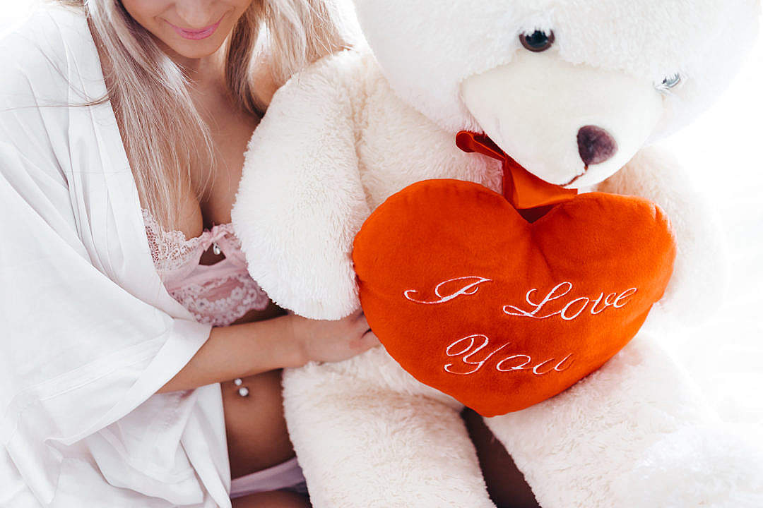 Download Smiling Woman and a Big White Teddy Bear with a Heart FREE Stock Photo