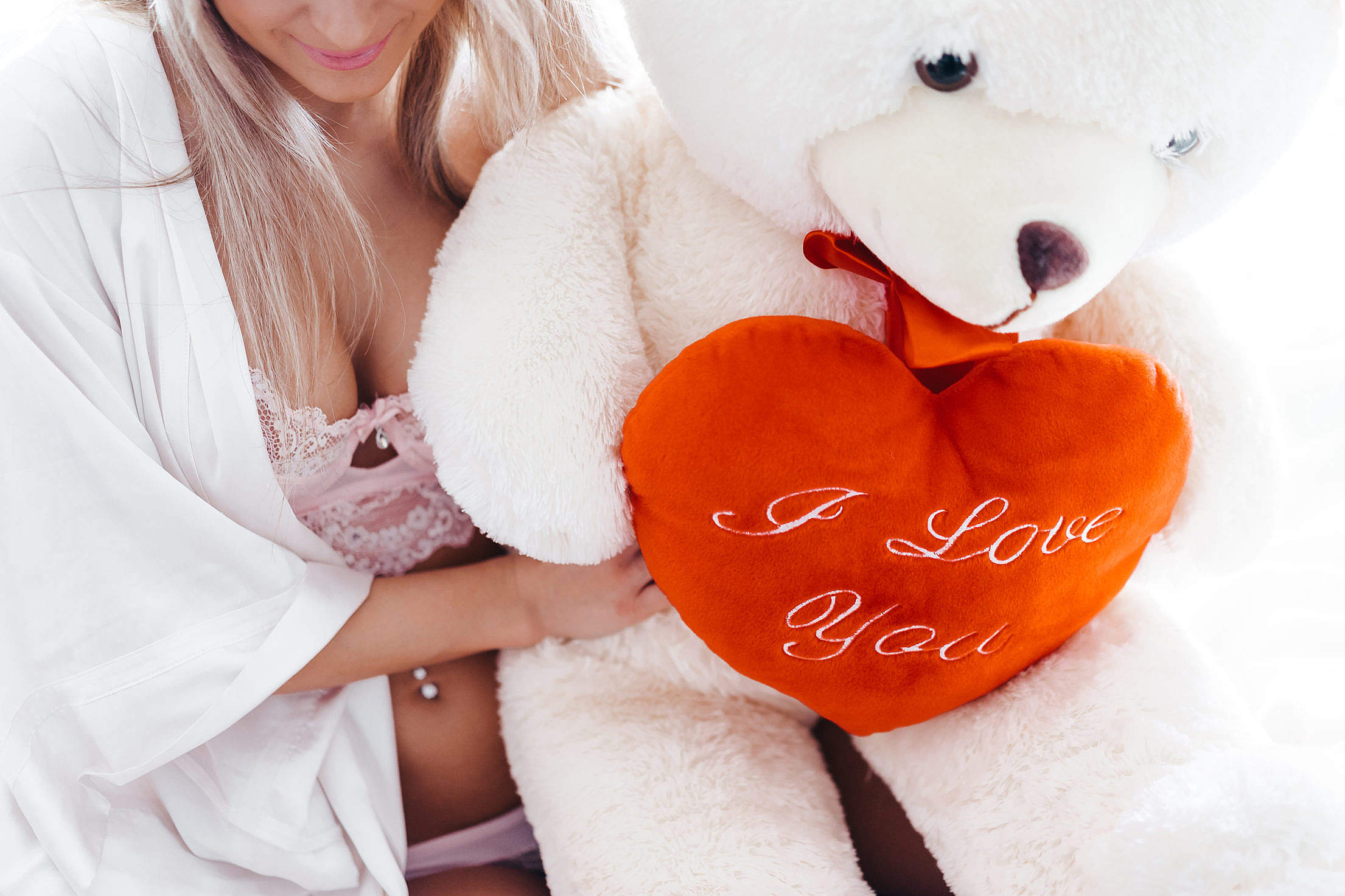 Smiling Woman and a Big White Teddy Bear with a Heart Free Stock Photo