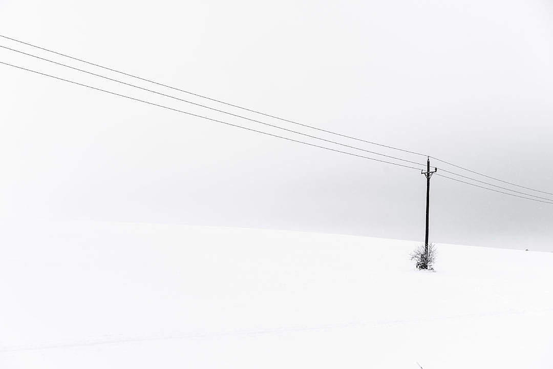 Download Snow Covered Hill and an Old Power Line Minimalistic FREE Stock Photo