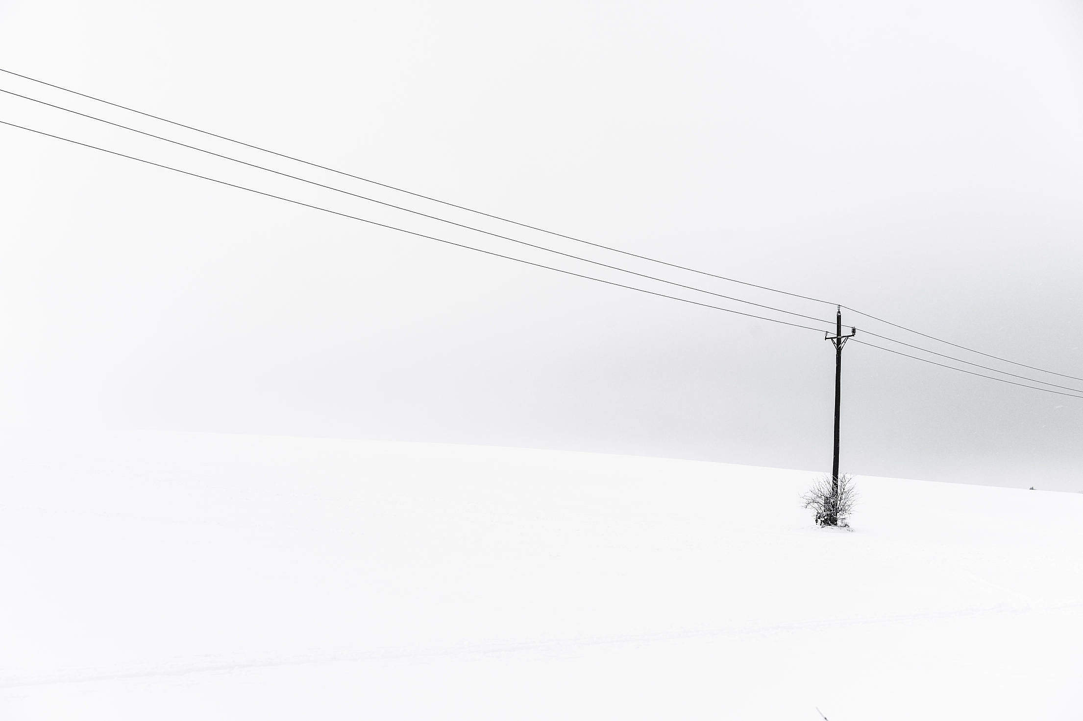 Snow Covered Hill and an Old Power Line Minimalistic Free Stock Photo