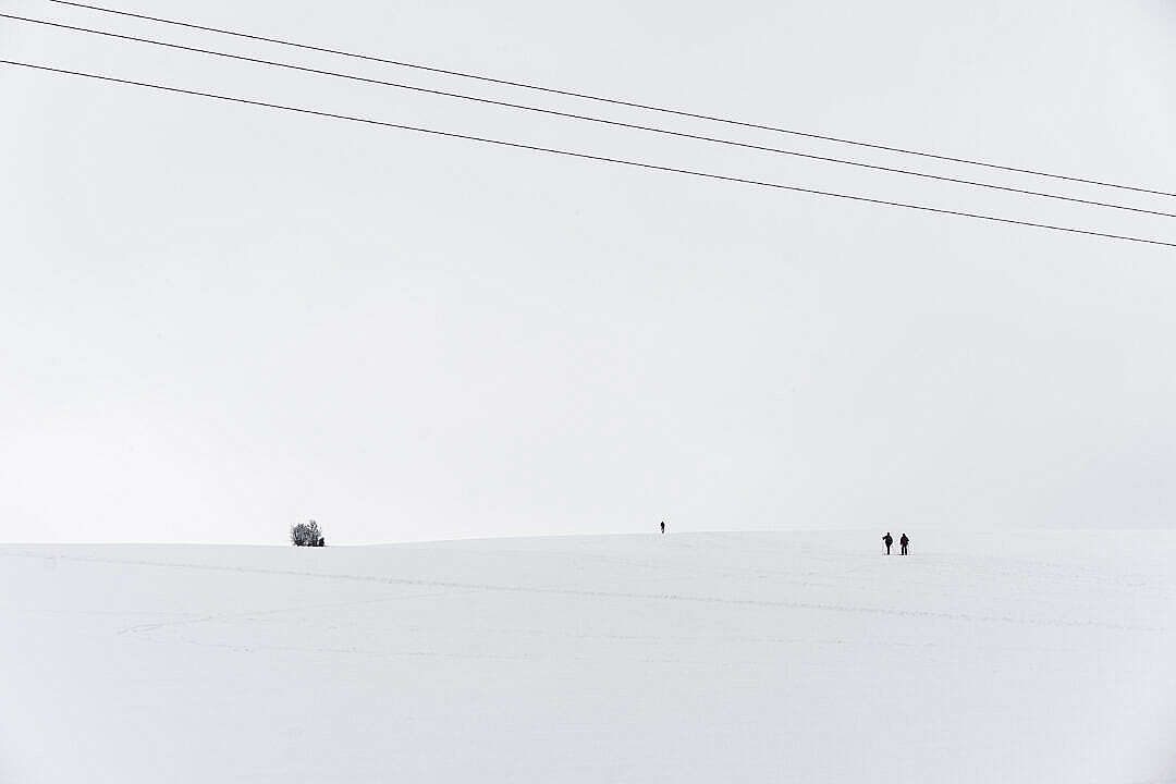 Download Snow Covered Hill with Tiny Cross-Country Skiers FREE Stock Photo