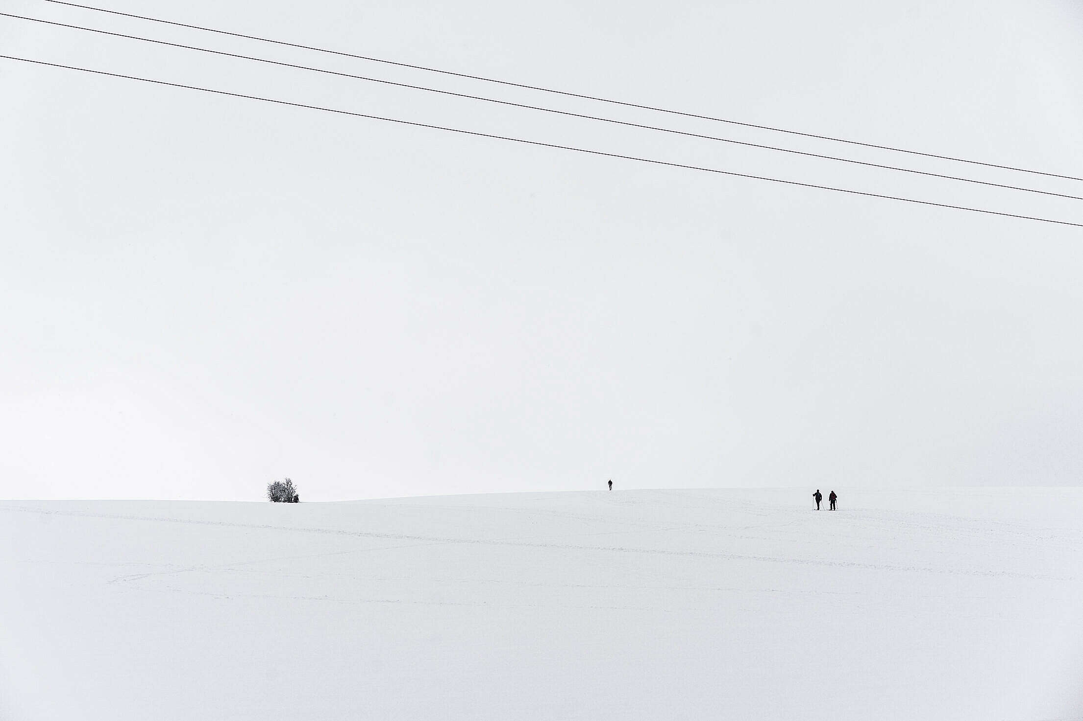 Snow Covered Hill with Tiny Cross-Country Skiers Free Stock Photo