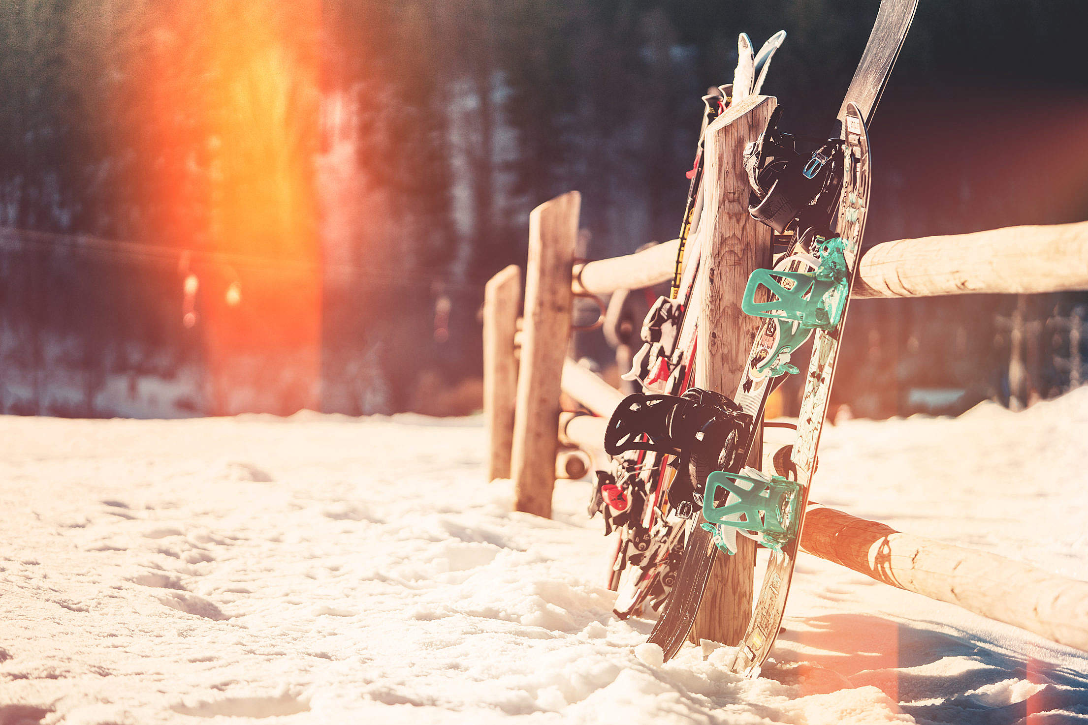 Snowboards and Skis Leaning Against Wooden Fence Free Stock Photo