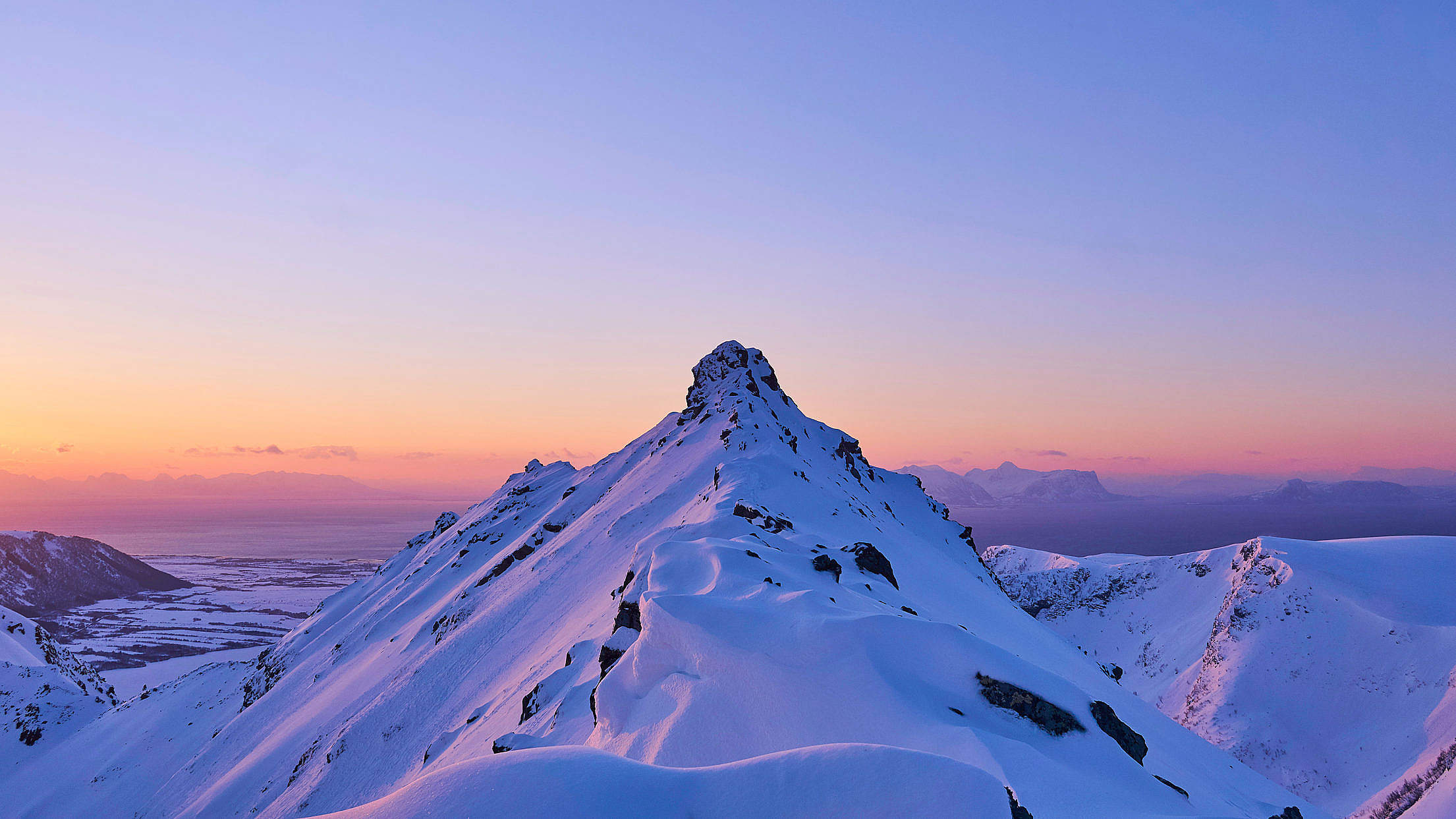 Snowy Mountain Peak with Sunrise Glow Free Stock Photo